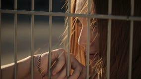 Όμορφη γυναίκα πίσω από τα κάγκελα απόθεμα βίντεο