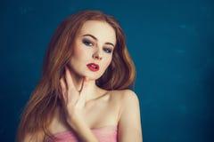 Όμορφη γυναίκα πορτρέτου κινηματογραφήσεων σε πρώτο πλάνο σε ένα μπλε υπόβαθρο Στοκ Εικόνες