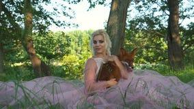 Όμορφη γυναίκα πορτρέτου που κρατά την κόκκινη αλεπού στα χέρια και το χαμόγελό της απόθεμα βίντεο