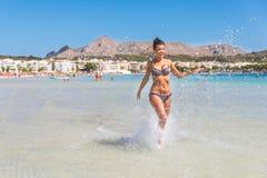 Όμορφη γυναίκα που έχει τη διασκέδαση στην παραλία στη Μαγιόρκα Στοκ Φωτογραφίες