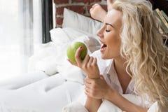 Όμορφη γυναίκα που έχει το πρόγευμα στο κρεβάτι με τη Apple Στοκ Φωτογραφίες