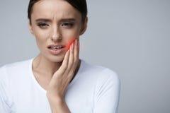 Όμορφη γυναίκα που αισθάνεται τον πόνο δοντιών, επίπονος πονόδοντος υγεία στοκ εικόνα