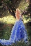 Όμορφη γυναίκα που απολαμβάνει τον ιώδη κήπο, νέα γυναίκα με τα λουλούδια στο πράσινο πάρκο εύθυμο περπάτημα εφήβων υπαίθριο μαλα στοκ φωτογραφία με δικαίωμα ελεύθερης χρήσης