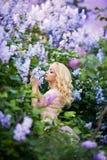 Όμορφη γυναίκα που απολαμβάνει τον ιώδη κήπο, νέα γυναίκα με τα λουλούδια στο πράσινο πάρκο εύθυμο περπάτημα εφήβων υπαίθριο μαλα στοκ εικόνες με δικαίωμα ελεύθερης χρήσης