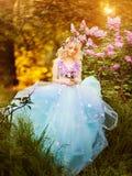 Όμορφη γυναίκα που απολαμβάνει τον ιώδη κήπο, νέα γυναίκα με τα λουλούδια στο πράσινο πάρκο εύθυμο περπάτημα εφήβων υπαίθριο μαλα στοκ φωτογραφία