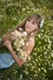 Όμορφη γυναίκα που απολαμβάνει τον τομέα μαργαριτών, συμπαθητικό θηλυκό που ξαπλώνει στο λιβάδι των λουλουδιών, όμορφη χαλάρωση κ Στοκ Εικόνες