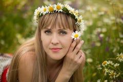 Όμορφη γυναίκα που απολαμβάνει τον τομέα μαργαριτών, συμπαθητικό θηλυκό που ξαπλώνει στο λιβάδι των λουλουδιών, όμορφη χαλάρωση κ Στοκ Εικόνα