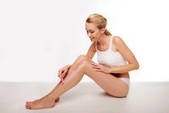 Όμορφη γυναίκα που αφαιρεί το τρίχωμα ποδιών της Στοκ εικόνες με δικαίωμα ελεύθερης χρήσης