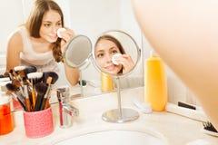 Όμορφη γυναίκα που αφαιρεί makeup μπροστά από τον καθρέφτη Στοκ Εικόνα