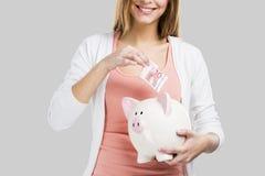 Όμορφη γυναίκα που βάζει τα χρήματα σε μια piggy τράπεζα στοκ εικόνες