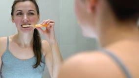 Όμορφη γυναίκα που βουρτσίζει τα δόντια της σε ένα λουτρό το πρωί Υγιεινή πρωινού απόθεμα βίντεο