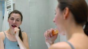Όμορφη γυναίκα που βουρτσίζει τα δόντια της σε ένα λουτρό το πρωί Υγιεινή πρωινού φιλμ μικρού μήκους