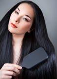 Όμορφη γυναίκα που βουρτσίζει το τρίχωμά της Στοκ Φωτογραφίες