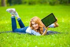 Όμορφη γυναίκα που βρίσκεται στη χλόη με την ταμπλέτα Στοκ Εικόνες