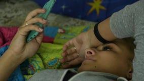 Όμορφη γυναίκα που βρίσκεται στο κρεβάτι και το κινητό τηλέφωνο χρήσεων κίνηση αργή απόθεμα βίντεο