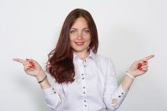 Όμορφη γυναίκα που δείχνει τα δάχτυλά της στις διαφορετικές κατευθύνσεις που απομονώνονται πέρα από ένα άσπρο υπόβαθρο στοκ εικόνα