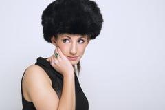 Όμορφη γυναίκα που διαμορφώνει ένα καπέλο γουνών Στοκ φωτογραφία με δικαίωμα ελεύθερης χρήσης