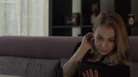 Όμορφη γυναίκα που εξετάζει στη συνεδρίαση PC ταμπλετών οθόνης τον καναπέ στον καφέ απόθεμα βίντεο