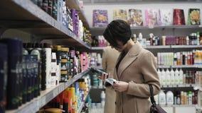 Όμορφη γυναίκα που εξετάζει τα καλλυντικά στην υπεραγορά φιλμ μικρού μήκους