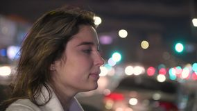 Όμορφη γυναίκα που εξετάζει την πόλη και τη σκέψη καμερών τη νύχτα φιλμ μικρού μήκους