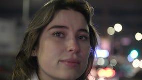 Όμορφη γυναίκα που εξετάζει την πόλη και τη σκέψη καμερών τη νύχτα απόθεμα βίντεο