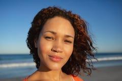 Όμορφη γυναίκα που εξετάζει τη κάμερα στην παραλία στην ηλιοφάνεια στοκ φωτογραφία με δικαίωμα ελεύθερης χρήσης