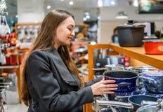Όμορφη γυναίκα που επιλέγει τα πιάτα εργαλείων σε μια υπεραγορά καταστημάτων στοκ εικόνες με δικαίωμα ελεύθερης χρήσης