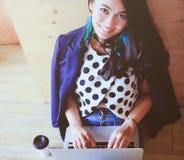 Όμορφη γυναίκα που εργάζεται με το lap-top στο ξύλινο πάτωμα στοκ εικόνα με δικαίωμα ελεύθερης χρήσης