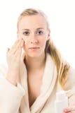 Όμορφη γυναίκα που εφαρμόζει την κρέμα στο μάγουλο Στοκ φωτογραφίες με δικαίωμα ελεύθερης χρήσης