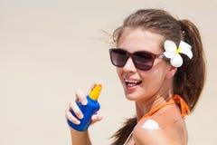 Όμορφη γυναίκα που εφαρμόζει τη suntan κρέμα Στοκ Φωτογραφίες