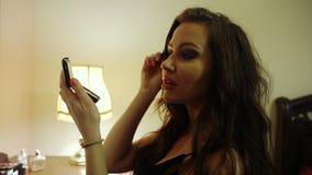 Όμορφη γυναίκα που εφαρμόζει mascara στα eyelashes της μπροστά από το μικρό καθρέφτη απόθεμα βίντεο