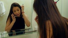 Όμορφη γυναίκα που εφαρμόζει mascara eyelash μπροστά από τον καθρέφτη, μιλώντας μέσω του smartphone στο λουτρό απόθεμα βίντεο