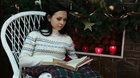 Όμορφη γυναίκα που διαβάζει ένα βιβλίο από την εστία απόθεμα βίντεο