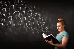 Όμορφη γυναίκα που διαβάζει ένα βιβλίο με τα ερωτηματικά που προέρχονται από Στοκ εικόνες με δικαίωμα ελεύθερης χρήσης