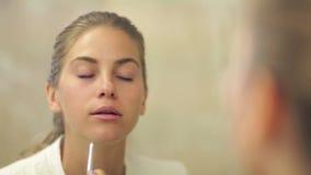 Όμορφη γυναίκα που ισχύει makeup στα χείλια απόθεμα βίντεο