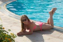 Όμορφη γυναίκα που κάνει ηλιοθεραπεία από τη λίμνη στοκ εικόνες