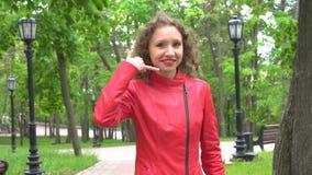 Όμορφη γυναίκα που κάνει μια κλήση μου χειρονομία και χαμόγελο απόθεμα βίντεο