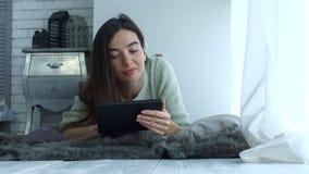 Όμορφη γυναίκα που κάνει σερφ το δίχτυ με το PC ταμπλετών φιλμ μικρού μήκους