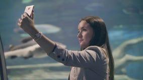 Όμορφη γυναίκα που κάνει την κινητή φωτογραφία selfie στα ψάρια υποβάθρου στο oceanarium απόθεμα βίντεο