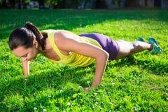 Όμορφη γυναίκα που κάνει την ώθηση επάνω στην άσκηση στο πάρκο Στοκ Εικόνα