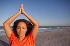 Όμορφη γυναίκα που κάνει τη γιόγκα στην παραλία στην ηλιοφάνεια στοκ φωτογραφία με δικαίωμα ελεύθερης χρήσης