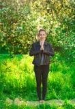 Όμορφη γυναίκα που κάνει τη γιόγκα υπαίθρια στην πράσινη χλόη στοκ φωτογραφία