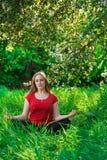 Όμορφη γυναίκα που κάνει τη γιόγκα υπαίθρια στην πράσινη χλόη Στοκ Εικόνες