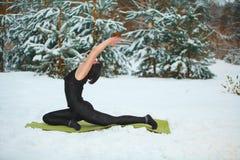 Όμορφη γυναίκα που κάνει τη γιόγκα υπαίθρια στο χιόνι Στοκ εικόνα με δικαίωμα ελεύθερης χρήσης