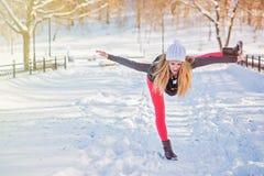 Όμορφη γυναίκα που κάνει τη γιόγκα υπαίθρια στο χιόνι Στοκ Φωτογραφίες