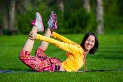 Όμορφη γυναίκα που κάνει τις ασκήσεις γιόγκας στο πάρκο στοκ εικόνα