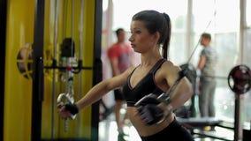 Όμορφη γυναίκα που κάνει τις ασκήσεις διασταυρώσεων καλωδίων στο workout, υγιής τρόπος ζωής απόθεμα βίντεο