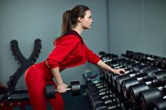 Όμορφη γυναίκα που κάνει τις ασκήσεις με τον αλτήρα στη γυμναστική Στοκ Φωτογραφίες