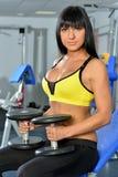 Όμορφη γυναίκα που κάνει τις ασκήσεις στην αθλητική λέσχη. στοκ εικόνες