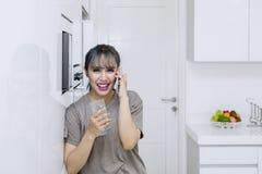 Όμορφη γυναίκα που κάνει το τηλεφώνημα στην κουζίνα στοκ φωτογραφία με δικαίωμα ελεύθερης χρήσης